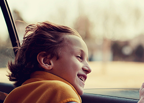 Boy with head out car window
