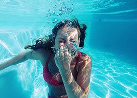 woman swimming holding breath underwater