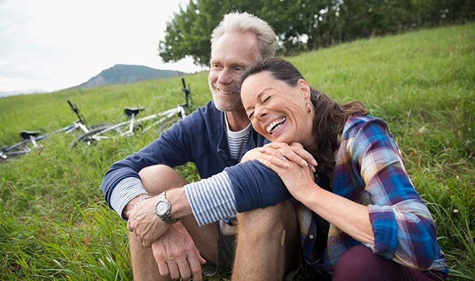 Older couple sitting on grass smiling