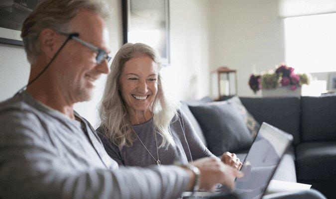 mature couple using ipad at kitchen table