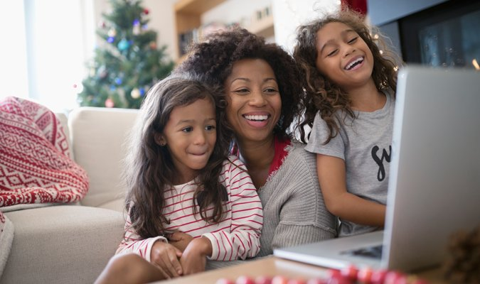 Mother with two daughters looking at laptop