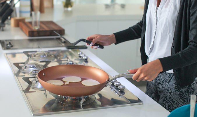 woman cooking pancakes over gas stove
