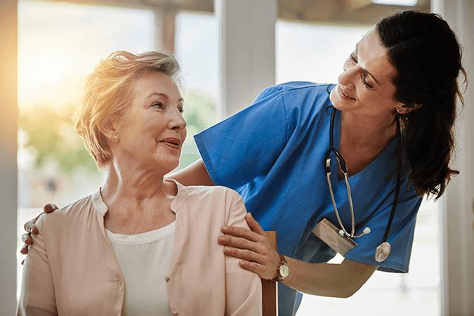 female nurse comforting female senior patient