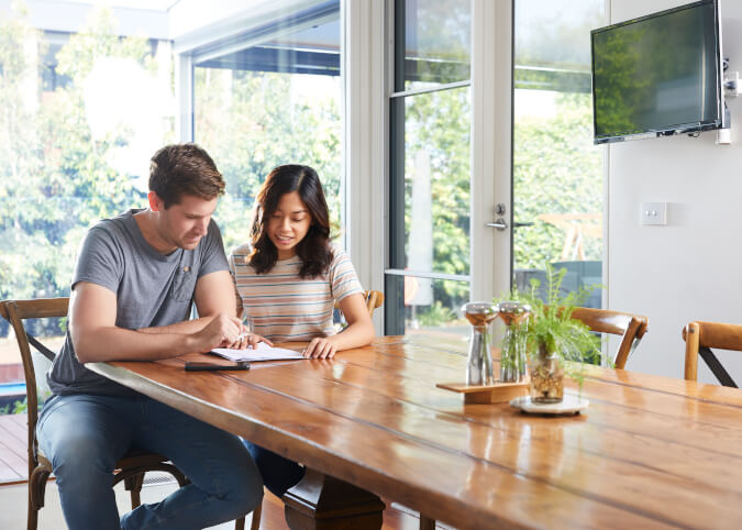 Young Australian couple reviewing paper bills at home