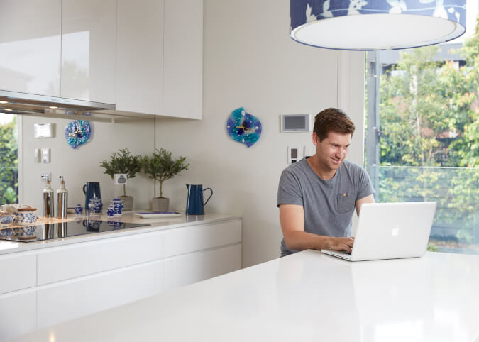 Man in modern kitchen on laptop