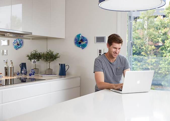 young man in kitchen with silver laptop