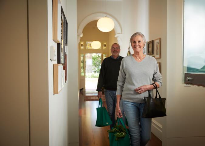 Mature couple walking down home hallway