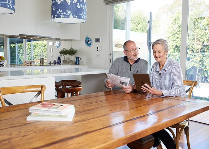 older couple with bills in kitchen