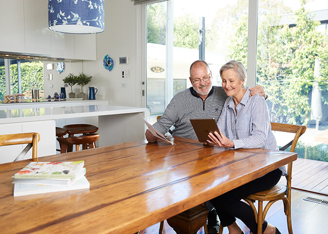 Older couple smiling looking at tablet