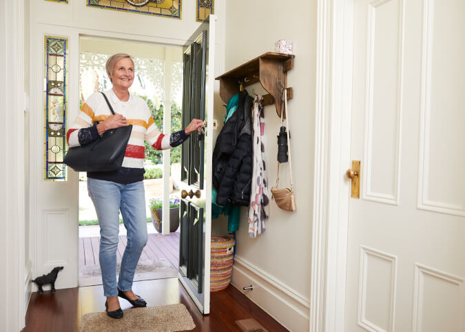 Woman walking into sunny hallway in her home