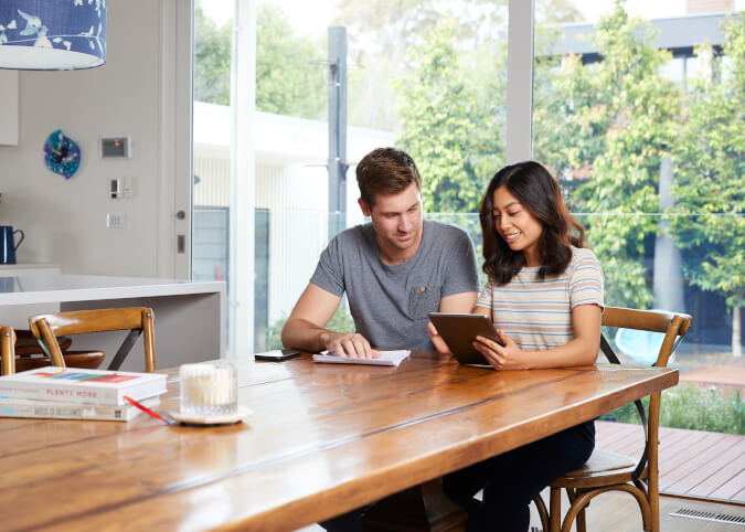 Couple with tablet comparing insurance policies at home