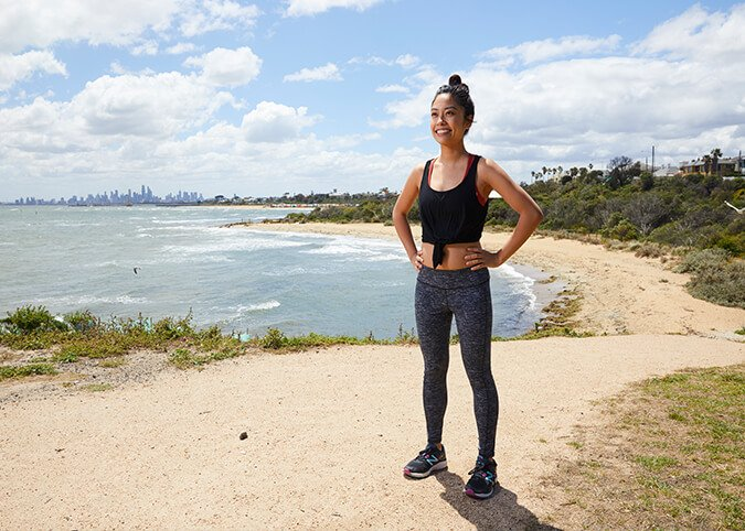 Young woman by beach in activewear