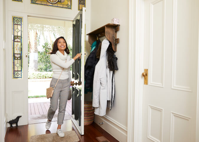 Young woman opening front door smiling