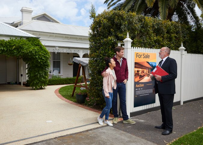 Auctioneer talking to couple who just bought home