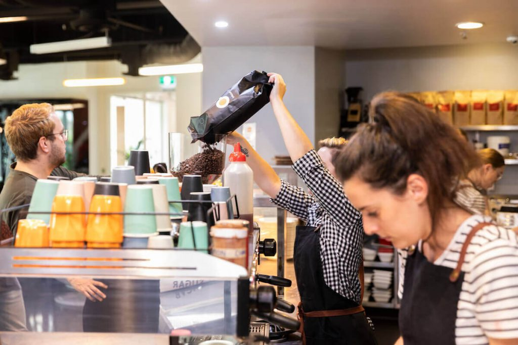 Barista refilling coffee beans in cafe in Australia