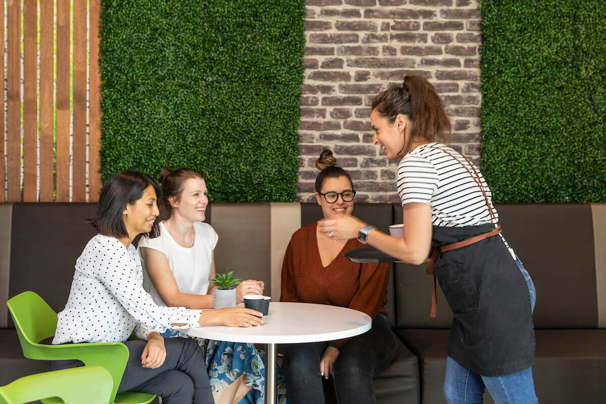 Waitress serving three women coffees in cafe