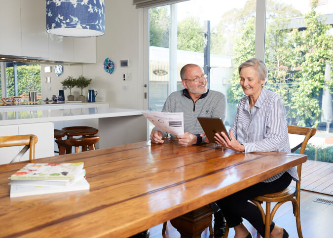 Mature couple looking at tablet at home