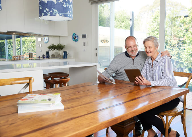 Mature couple smiling and looking at ipad