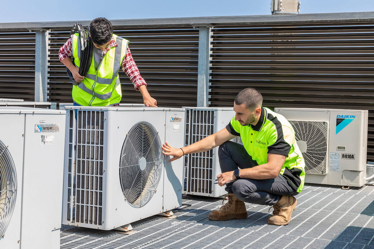 Two Australian tradesmen inspecting air conditioner