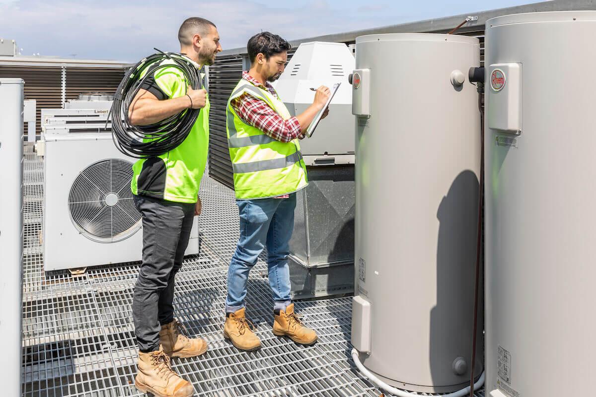 Two tradies performing hot water building maintenance