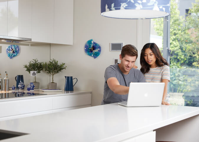 Young couple looking at silver laptop