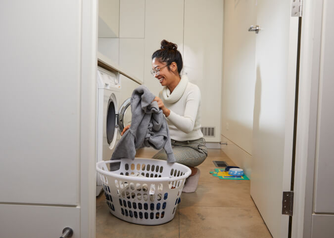 woman smiling doing laundry at home