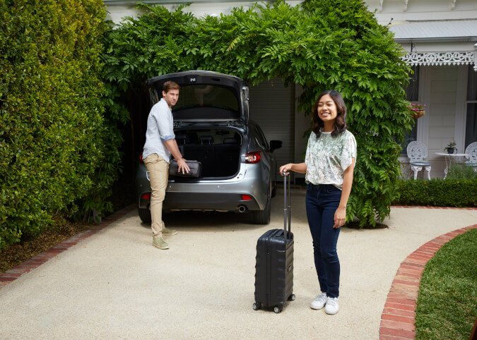 Couple loading suitcases into car in driveway