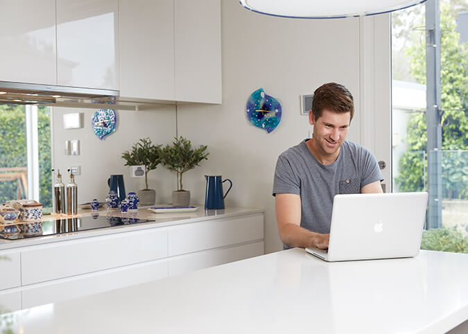 man with silver laptop in kitchen