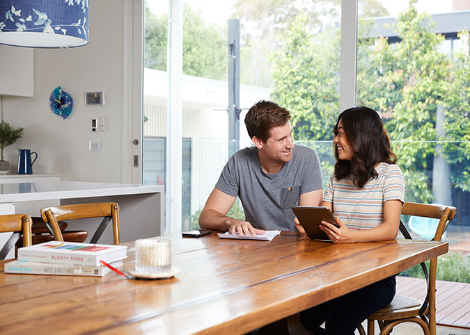 couple smiling at dining room table with tablet
