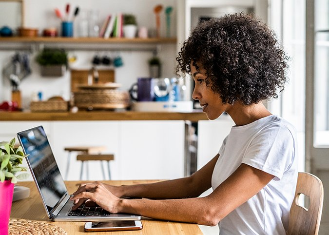 curly haired woman using laptop