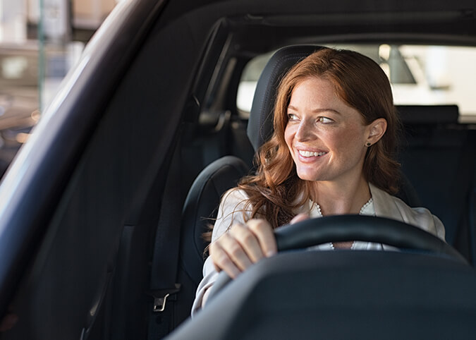 redhead woman driving car