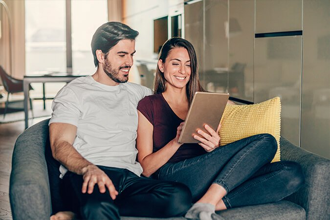 Young couple using tablet device at home